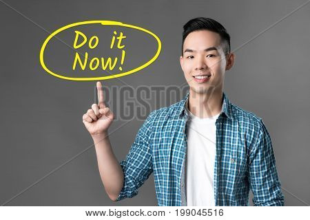 Young cheerful empowered Asian man pointing to