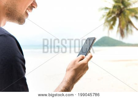 Male tourist using smart phone on the island at the beach in summer vacation - mobile roaming concept