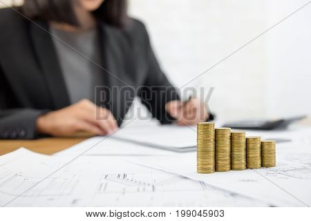 Businesswoman reviewing document with money and blueprints on the table - real estate and properties investment concepts