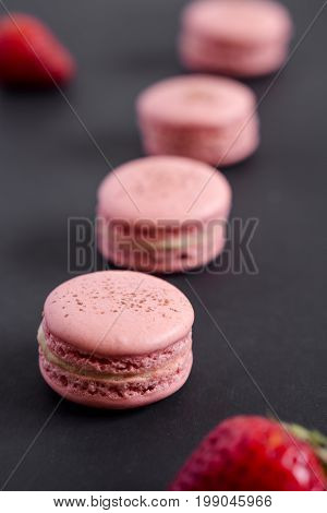 Strawberry macarons on dark background. Macarons are delicate french pastries made of round meringue cookies and a sweet filling in the center. Light & crisp the perfect dessert.