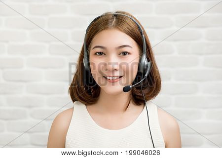 Casual Asian businesswoman wearing microphone headset as a telemarketing customer service agent call center job concept