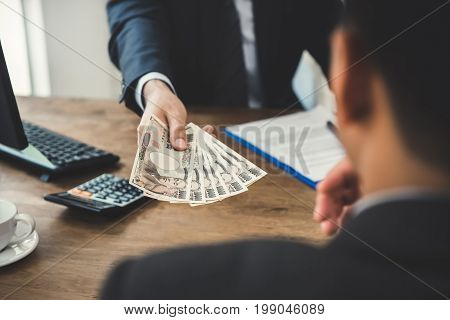 Businessman giving money Japanese yen currency to his partner while making contract - loan and bribery concept