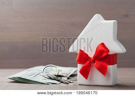 Small white house decorated red bow ribbon with bunch of keys and cash money on wooden table. Gift, real estate, purchase or buying a new home concept.