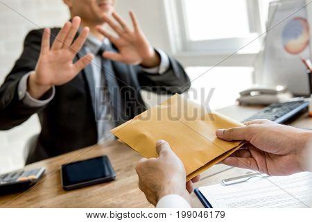 Businessman rejecting money in the envelope offered by his partner - anti bribery concept