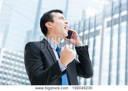 Winning businessman talking on mobile phone in the city clenching his fist feeling great and delighted - success and achievement concepts