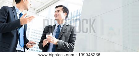 Friendly businessmen talking outdoors while going to work in the morning - panoramic web banner background with copy space