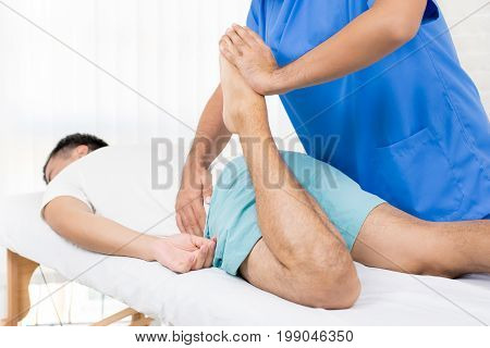 Physiotherapist stretching leg of male patient on the bed in hospital - physical therapy concept