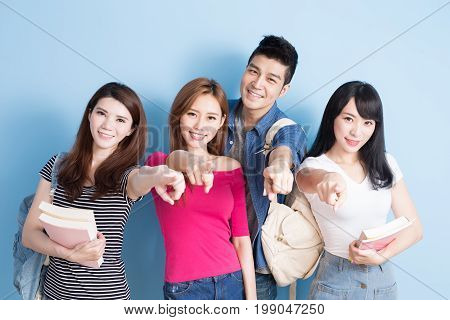 happy group student pointing you on the blue background