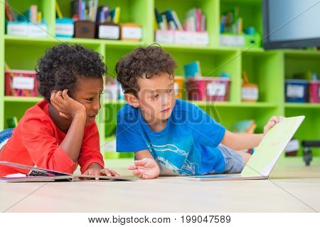 Two boy kid lay down on floor and reading tale book in preschool libraryKindergarten school education concept.