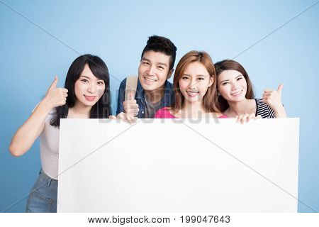 happy group student take billboard and show thumb up on the blue background