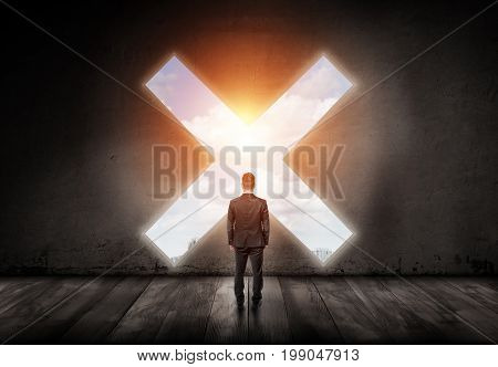 A businessman stands with his turned back and looks into a cross-shaped hole in a concrete wall. Time to stop. Avoid business pitfalls. Trouble ahead.