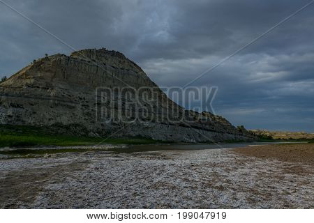 Rock formation behind Little Missouri river with cloudy skies in Theodore Roosevelt National Park North Dakota