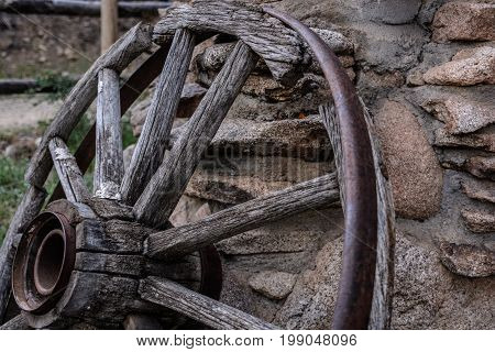 close up of old covered wagon wheel in disrepair leaning against a wall of stone