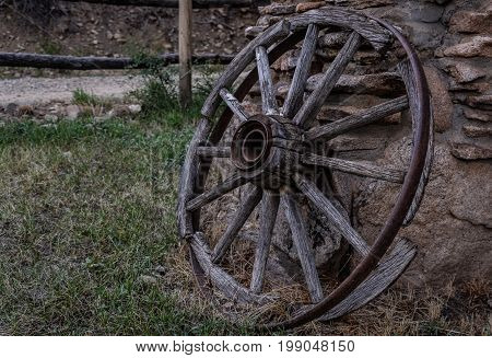 old covered wagon wheel in disrepair leaning against a wall of stone