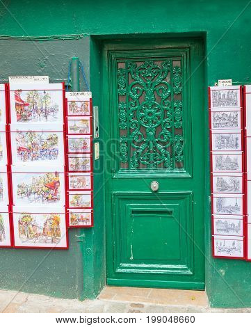PARIS, FRANCE - JUNE 6, 2012: A green door and art prints in Montmarte in Paris.