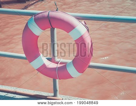 Retro filter color, lifebuoy ring hanging on the dock, water safety equipment.