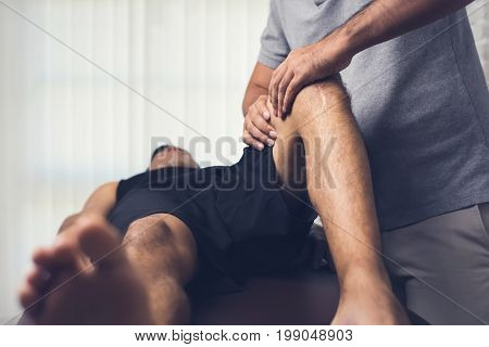 Therapist treating injured knee of athlete male patient in clinic - sport physical therapy concept