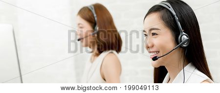 Beautiful smiling Asian woman telemarketing customer service agent team call center job concept - panoramic web banner