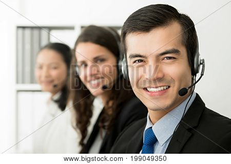 Smiling cheerful male telemarketing customer service agent with his team call center job concept