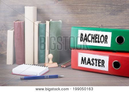 Bachelor and Master. Binders on desk in the office. Business background.