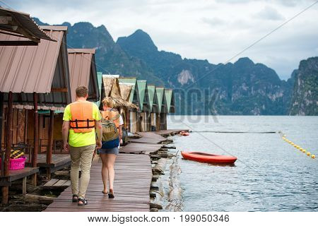 Traveler relaxing summer trip walking over wooden bridge on the asia lake with reflection sunlight background