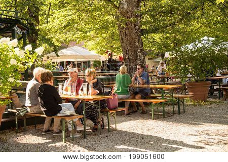 MunichGermany-August 072017: People relax in the afternoon while drinking in a local biergarten under its trees.