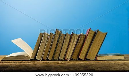Books on an old wooden table. Beautifu bluel background.