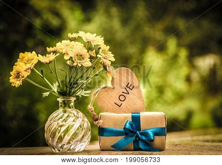 A bunch of yellow flowers a gift and a wooden heart. Romantic concept. Vintage tinting