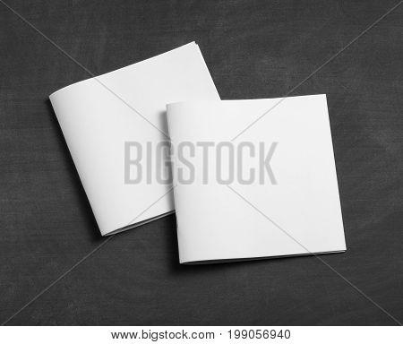 Blank white brochure on a black chalkboard