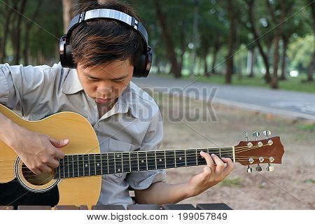 Portrait of musician or guitarist playing acoustic guitar in blurred nature with copyspace background.