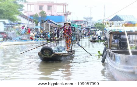 Soc Trang, Vietnam - January 21, 2017: Ferryman rowing takes visitors across  river to visit floating market, this is main transportation in river water festival Lunar New Year in Soc Trang, Vietnam.