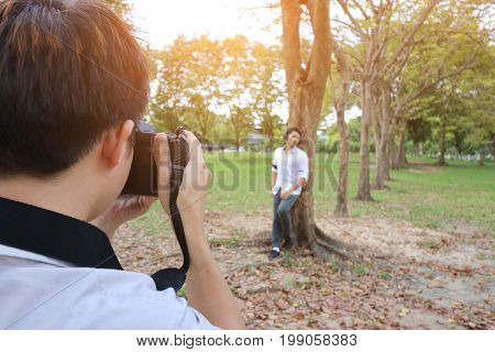Back view of photographer taking a photo of young man in summer park. Sunshine effect. Vintage tone/