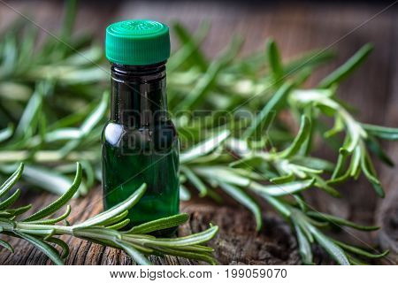 Rosemary essential oil and fresh rosemary on wooden background