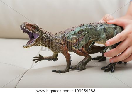 kids hand catching a brown Carcharodontosaurus and a green tyrannosaurus toy on a sofa at home