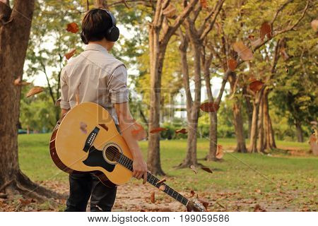 Rear view of portrait of handsome young man holding acoustic guitar with headphones against among falling leaves in the park outdoors