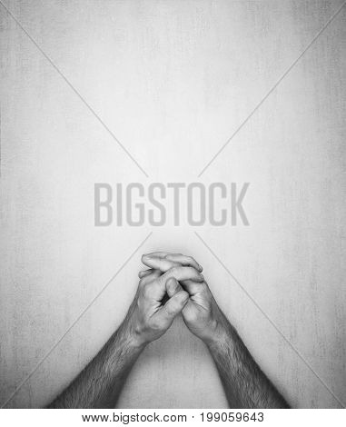 hands of a man are folded into a lock on a gray background top view. black and white photo mock up for text phrases lettering