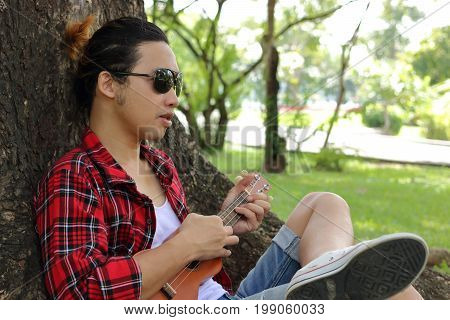Young hipster man is relaxing against ukulele in outdoor park.