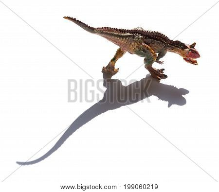 front view brown carnotaurus toy with shadow on a white background