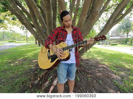Wide angle shot of portrait of handsome young man playing acoustic guitar in the park outdoors with a large tree background.
