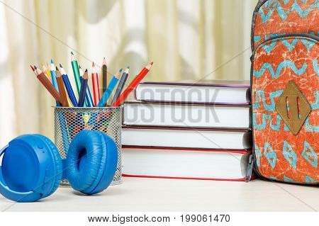 School Backpack With School Supplies. Books, Stand For Pencils With Color Pencils And Headphones On