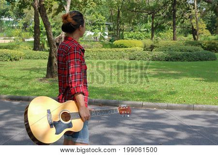 Portrait of young hipster man holding acoustic guitar in nature with copy space background.