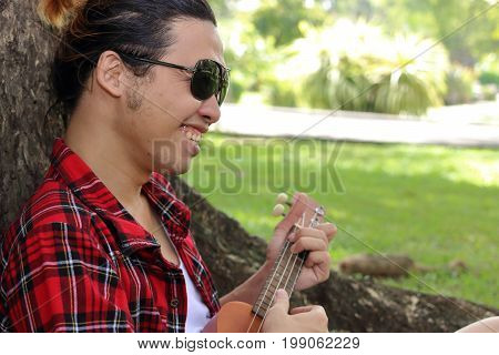 Young man playing ukulele in the park outdoor. He is smiling