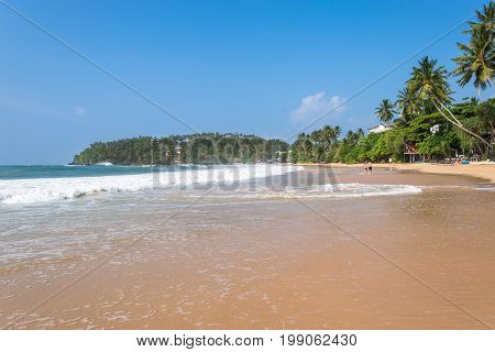 The white sandy beach and bay of Mirissa. The beach at the south coast is very popular among surfer. It is also a fishing port and one of the islands main whale- and dolphin watching locations