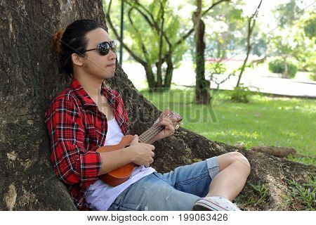 Portrait of young relaxed man is lying and play the ukulele at the public outdoor park.