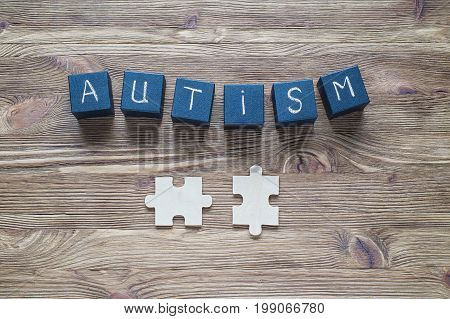 Autism awareness. Autism Spectrum Disorder (ASD). Black wooden cubes with word AUTISM and puzzles on a wooden background top view flat lay. Concept of autism word.