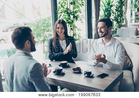 Three Young Happy Business Partners Are Celebrating, Sitting In Cafe, Wearing Suits, Smiling, Applau