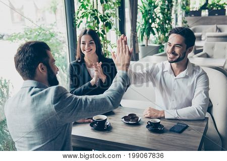 Success And Agreement Between Three Business Partners, They Celebrate Sitting In Cafe, Wearing Suits