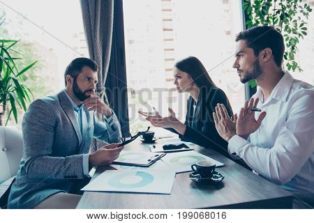 Three Business Partners In Smart Wear Are Discussing The Finances Of Their Company In A Meeting In R