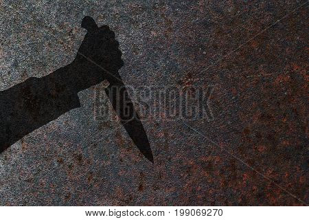 Human hand with killing knife silhouette in shadow on rust wall background. Illustration for criminal news and chronicles.