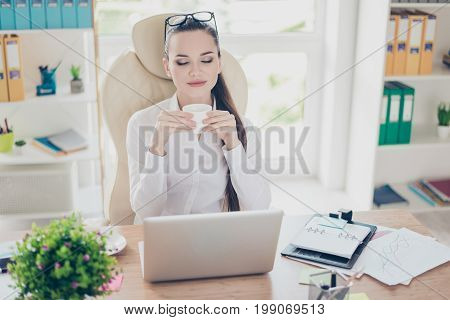 Morning In The Office. Young Pretty Business Lady Economist Is Enjoying Coffee At Her Work Ststion,